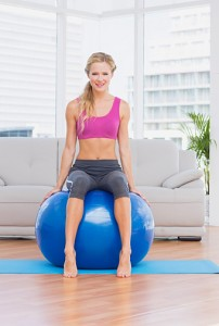 Toned blonde sitting on exercise ball smiling at camera